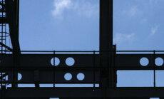 Darbininkas eina geležine konstrukcija statybose Londone