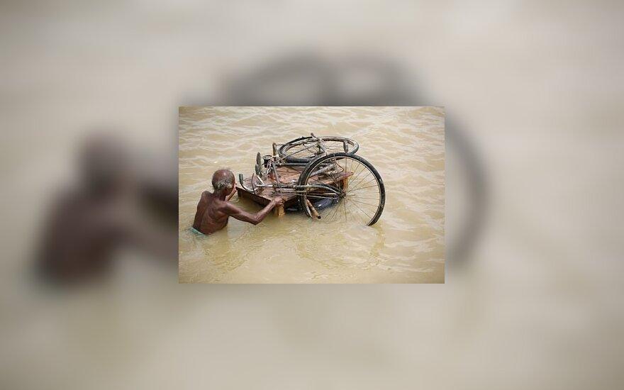 Rytų Indiją niokojant potvyniams, vyras ant lentų plukdo savo dviratį.