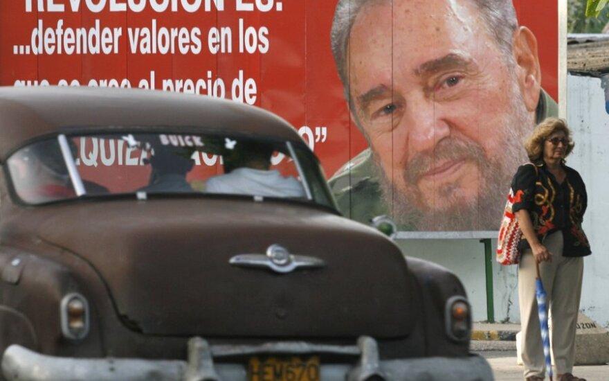 Senas automobilis rieda pro buvusio Kubo lyderio Fidelio Castro portretą Havanoje.