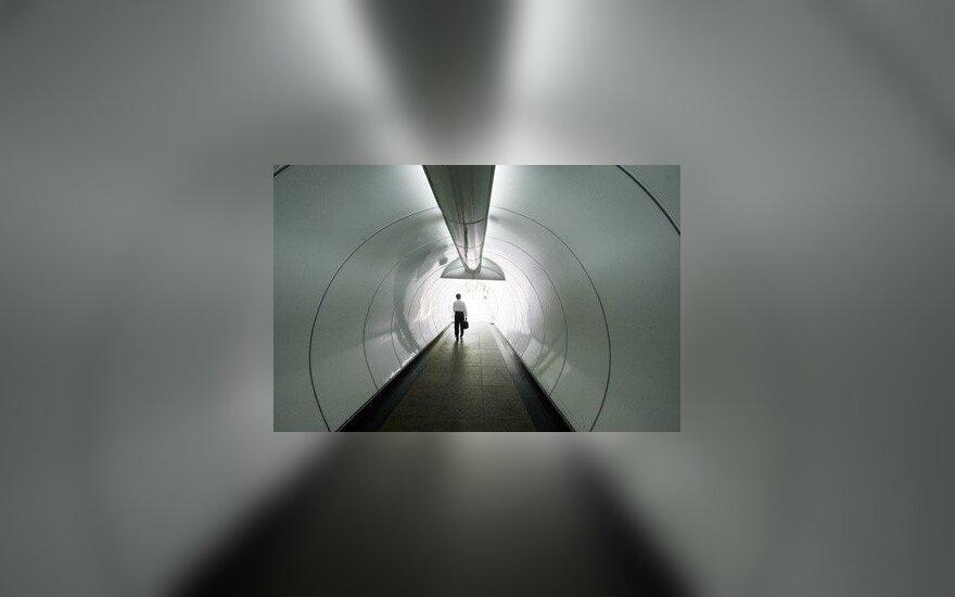 Verslininkas eina tuneliu, esančiu finansiniame Singapūro centre.
