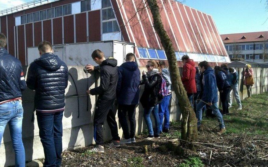 Solecznicka młodzież zamalowuje napis obrażający Polaków