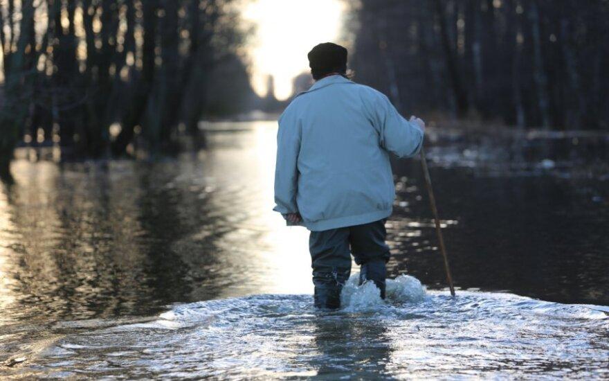 Žmonės iki savo sodybų keliauja per vandenį