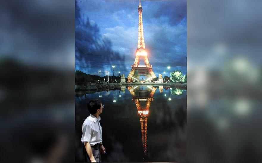 Vyras eina pro milžinišką ekraną su Eifelio bokšto atvaizdu Honkongo parke.