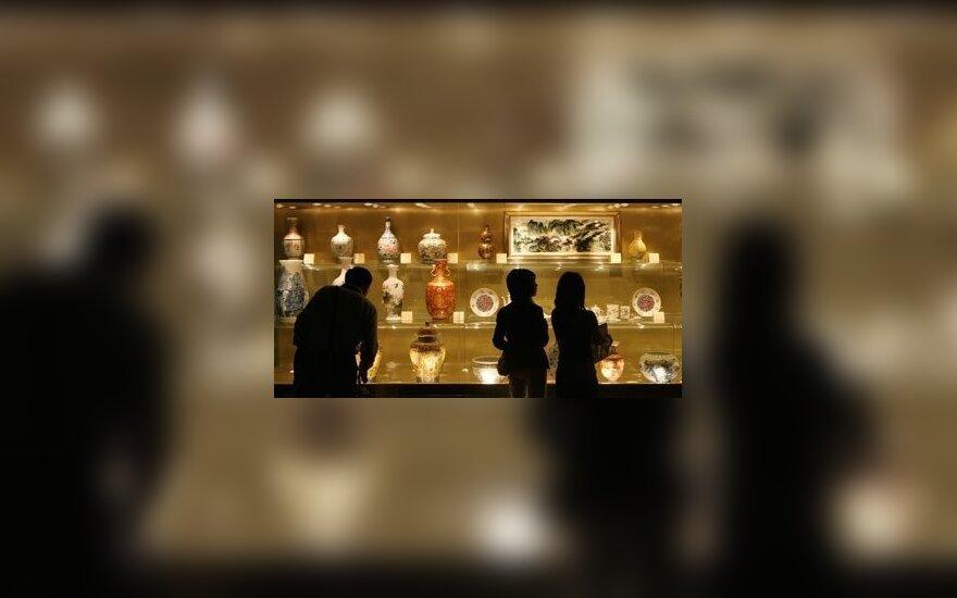 Lankytojai apžiūrinėja kiniškus antikvarinius indus.