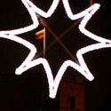 Pro Pilies gatvėje ore kybančią kalėdinę žvaigždę matyti Lietuvos vėliava ir Gedimino pilies fragmentas