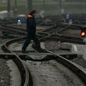 Darbininkas eina per geležinkelio bėgius