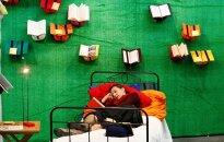 Moteris skaito knygą Frankfurto knygų mugėje.