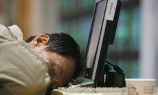 Nuvargęs vyras miega prie kompiuterio.