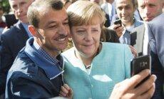 Vokietijos kanclerė A. Merkel pozuoja nuotraukai su pabėgėliu
