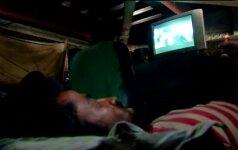 Nelegalus kino teatras po tiltu padeda indų rikšų traukikams atsipalaiduoti