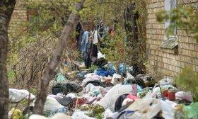 Kaimynai baiminasi žiurkių ir virusų: į negyvenamo namo kiemą benamis maišais tempia visokio plauko daiktus
