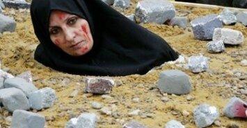 Iranietė moteris, vaizduodama akmenimis užmuštą auką, protestuoja BriuselyjeIranietė moteris, vaizduodama akmenimis užmuštą auką, protestuoja Briuselyje. Asociatyvinė nuotr.