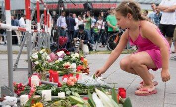 Mergaitė deda gėles šalia žudynių Miunchene vietos.