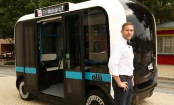 Local Motors steigėjas ir vadovas John B. Rogers šalia kompanijos kūrinio – kalbančio autobusiuko Oli