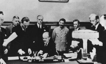 Molotovo-Ribbentropo pakto pasirašymas 1939 m. rugpjūčio 23 d. Prie stalo sėdi Viačeslavas Molotovas, už jo stovi Joachimas von Ribbentropas ir Josifas Stalinas.