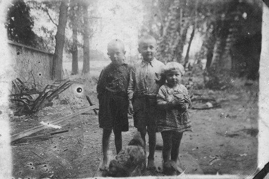 Kalvio vaikai su draugu prie senosios dvaro kalvės. Vis dar išlikęs tas pats pastatas, nuotraukoje matyti siena, prie kurios buvo rišami kaustomi arkliai (Pakruojo dvaro nuotr.)