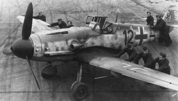 """Vokiečių aerodromo aptarnaujantis techninis personalas apsuka """"Messerschmitt Bf-109 G""""."""