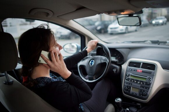 Pokalbis telefonu prie vairo. Asociatyvi nuotr.