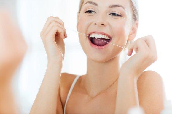 Dantų valymas tarpdančių siūlu.