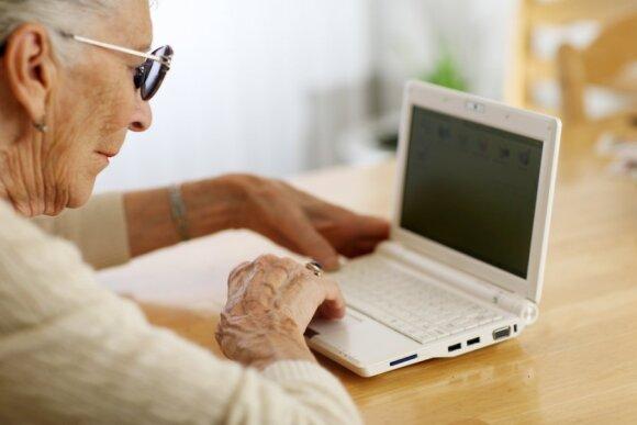 Sena moteris naudojasi kompiuteriu