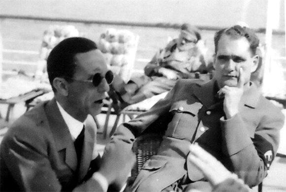 Kiek siurrealistinis Josepho Goebbelso ir Rudolfo Hesso vaizdas Berchtesgadene. Už jų matyti ant šezlongo snaudžiantis Hitleris.