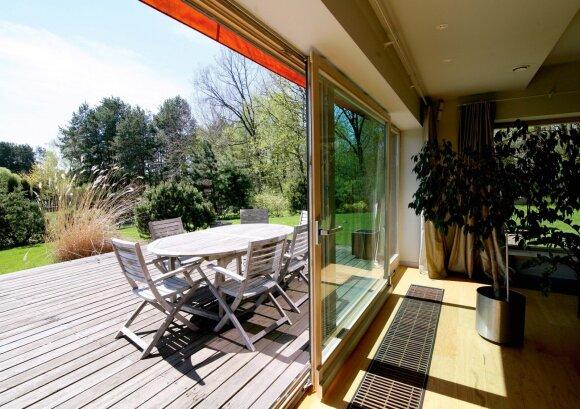 """Medinė terasa įrengta pietų pusėje, todėl yra saulėta (""""jei tik apskritai šviečia saulė, – Lietuvoje ji pasirodo retai"""")"""