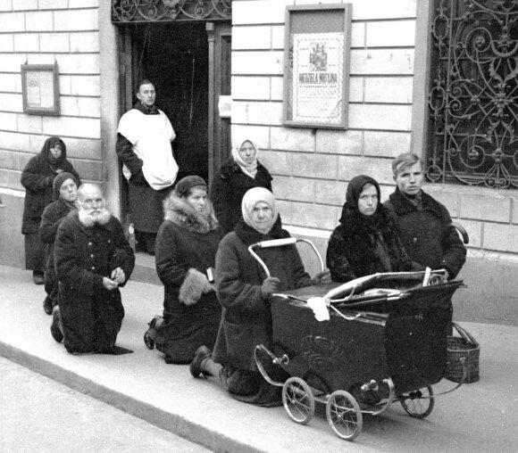 Aušros Vartų gatvė. Žmonės meldžiasi prieš Aušros Vartų koplyčioje kabantį Švč. Mergelės Marijos paveikslą, 1934 m. W. van de Poll, NA.