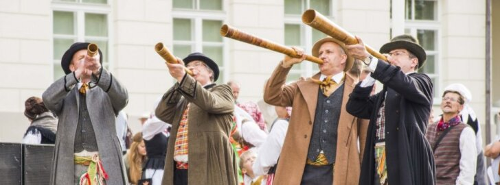 Men in traditional Lithuanian costumes playing the ragas