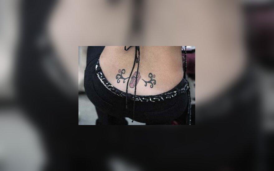 """Moteris, nugaroje išsitatuiravusi """"Rolling Stones"""", eina į grupės koncertą Bostone. 2005."""
