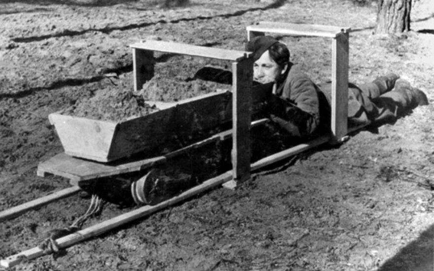 Vokiečių sargybinis demonstruoja, kaip savadarbiais bėgiais tunelyje stumti vėžimėliai.