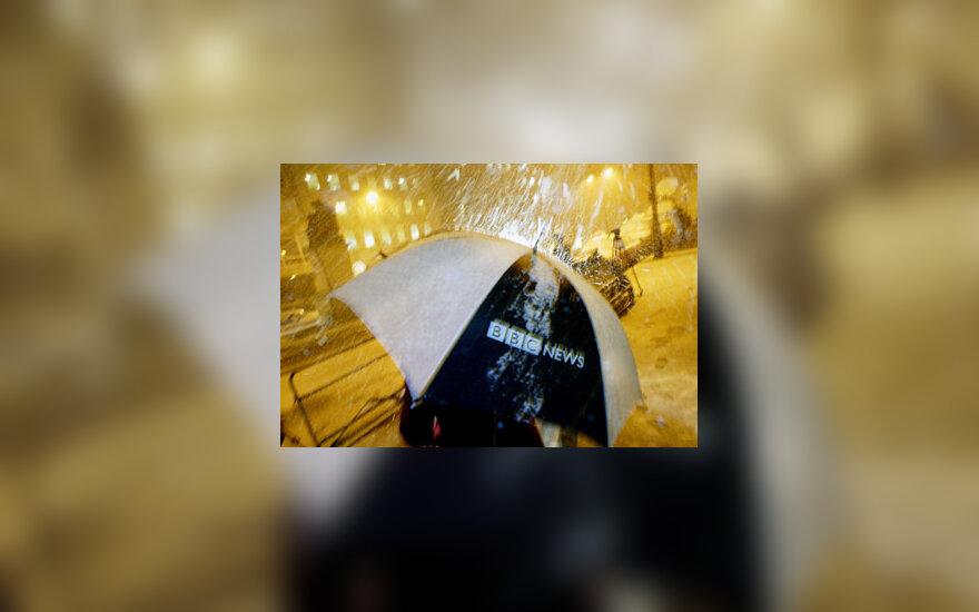 BBC darbuotojas eina su bendrovės logotipu papuoštu skėčiu
