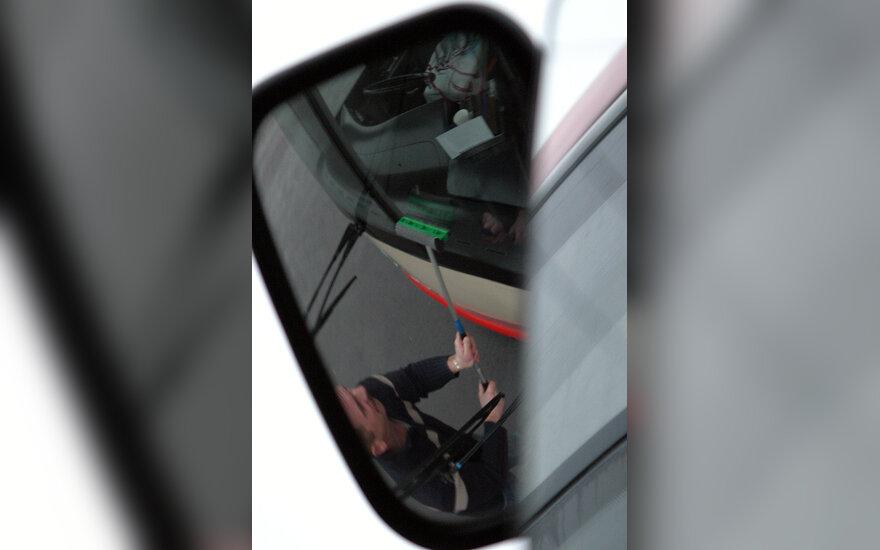 Troleibuso veidrodėlyje matyti kaip vairuotojas plauna priekinį stiklą