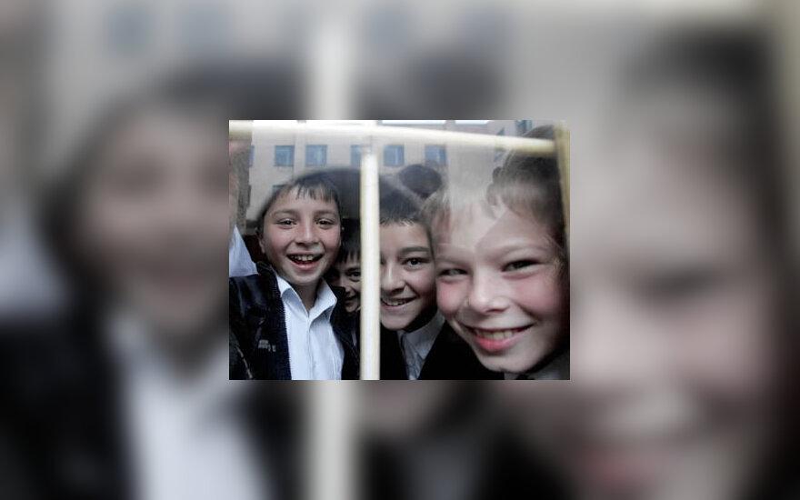 Beslano 6-osios mokyklos mokiniai žiūri pro langą.