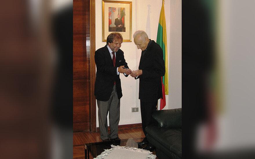 Ambasadorius Šarūnas Adomavičius įteikia pasą prelatui Stasiui Žiliui