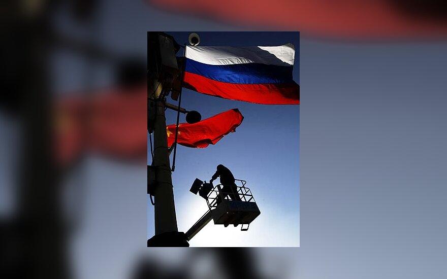 Darbininkas Pekino Tianenmenio aikštėje kabina Kinijos ir Rusijos vėliavas