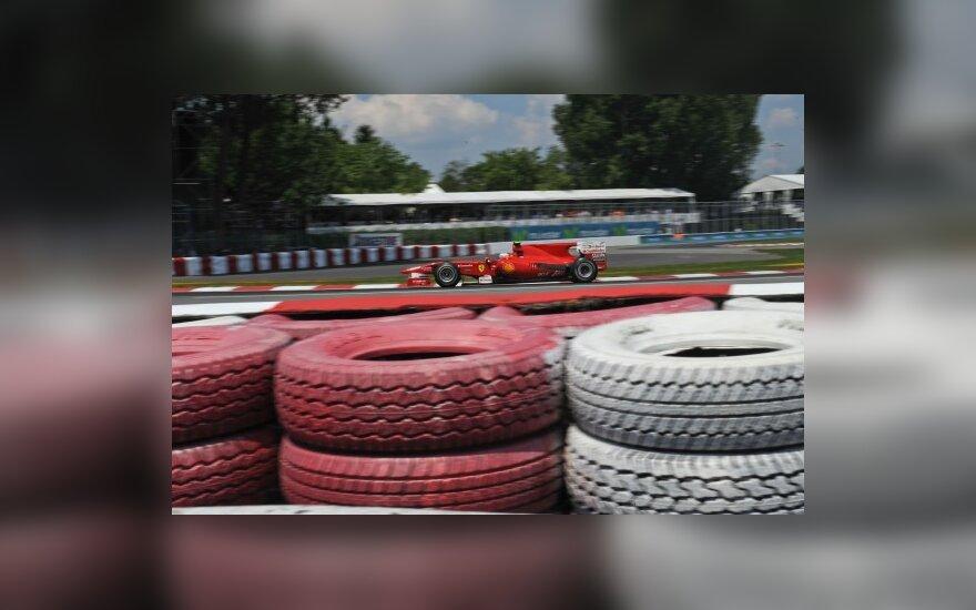 """F-1 """"Ferrari"""" automobilis važiuoja pro padangų užtvarą"""