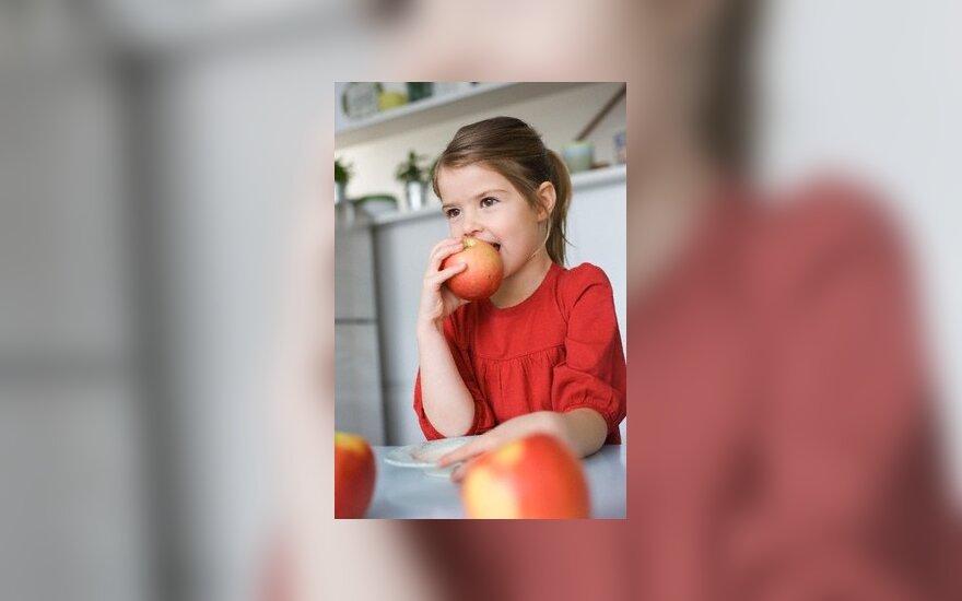 Mergaitė graužia obuolį