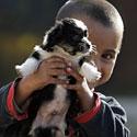 Vaikas žaidžia su šuniuku.