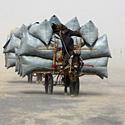 Vyras keliauja vežimu per dykumą smėlio audros metu