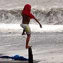 Filipinuose berniukas pajūryje balansuoja atsistojęs ant medinio kuolo