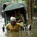 Indas rikša užtvindyta Kalkutos gatve tempia vežimėlį su moterimi.