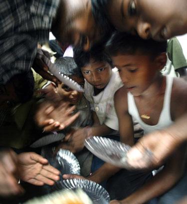 Nukentėjusiems nuo cunamio Indijos vaikams dalijamas maistas.