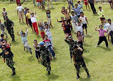 Vaikai Sumatros saloje išlydi maisto atgabenusį JAV sraigtasparnį