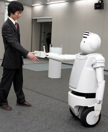 """Japonijos elektronikos konglomerato Hitachi sukurtas naujas robotas """"Emiew"""" demonstruoja savo sugebėjimus."""